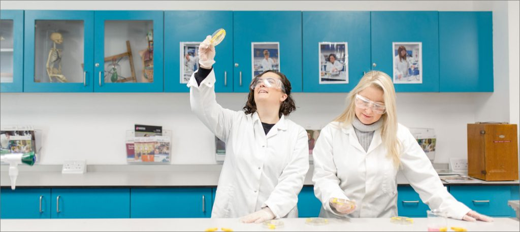 A student holding up a science dish in a laboratory