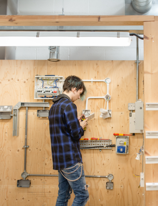 http://A%20student%20working%20in%20an%20electrician%20training%20room