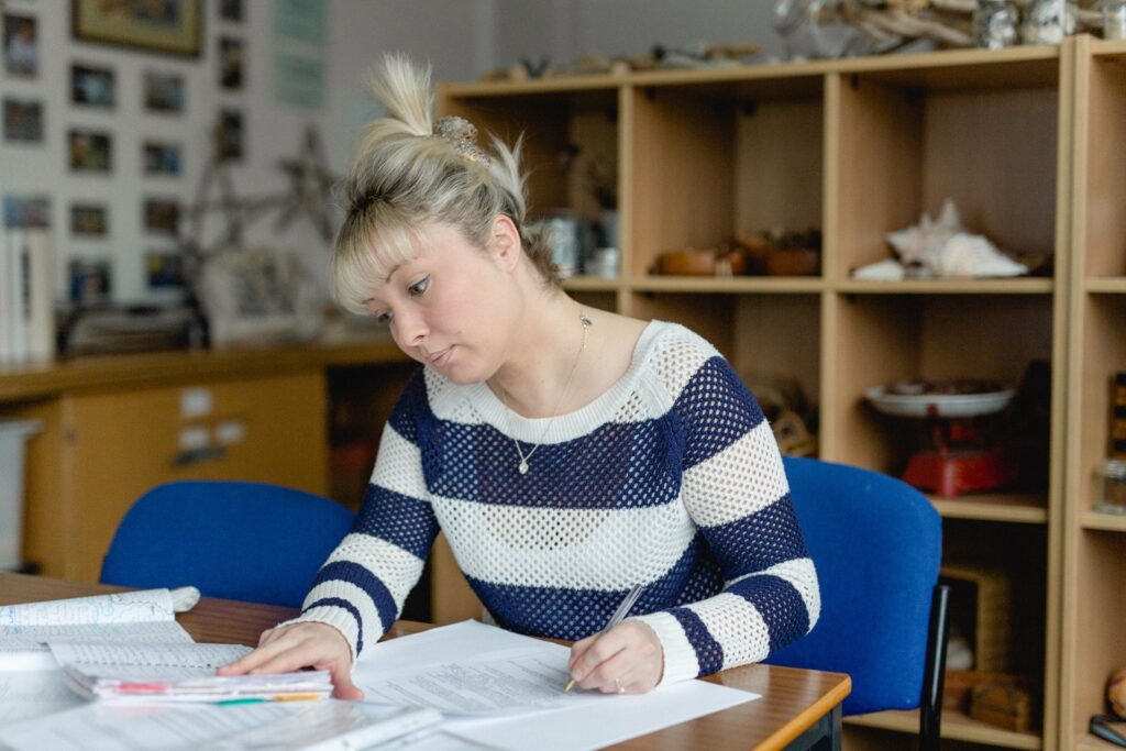 A blonde haired woman with a stripped jumper sat at a desk writing